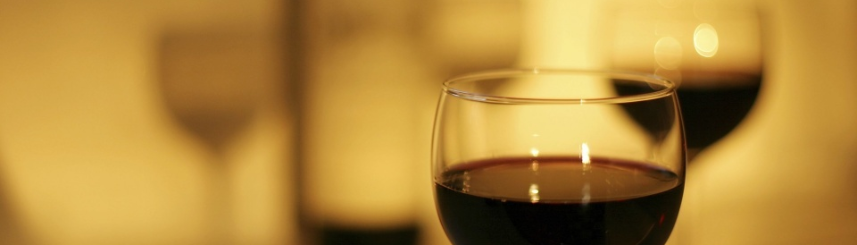 Zdjęcie przedstawia kieliszki z winem oraz butelkę w tle