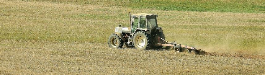 Zdjęcie przedstawia traktor pracujący na polu