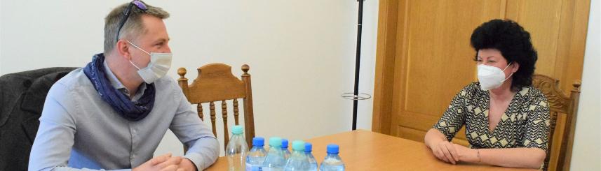 Zdjęcie przedstawia dwie osoby siedzące przy stole, na którym znajdują się dokumenty, telefony komórkowe oraz butelki z wodą