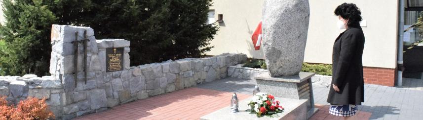 Na zdjęciu wójt gminy stoi przed tablicą poświęconą poległym powstańcom