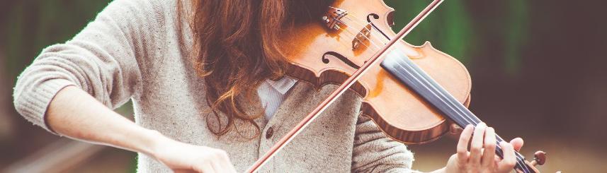 Zdjęcie przedstawia kobietę grającą na skrzypcach