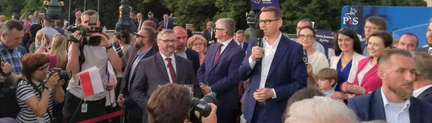 Premier Mateusz Morawiecki podczas spotkania z mieszkańcami przed Muzeum Zamkowym w Pszczynie. Premier stoi z mikrofonem, wokół premiera tłum ludzi oraz osoby z aparatami fotograficznymi