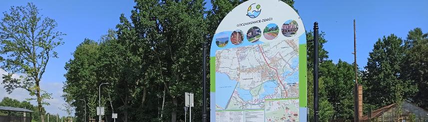 Zdjęcie przedstawia tablicę z mapami gminy zamontowaną na centrum przesiadkowym, w tle drzewa oraz tory