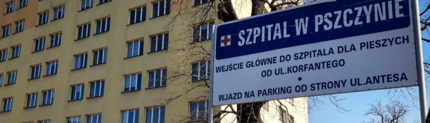 Zdjęcie przedstawia tablicę informacyjną oraz część budynku Szpitala Powiatowego w Pszczynie (źródło: Starostwo Powiatowe w Pszczynie)