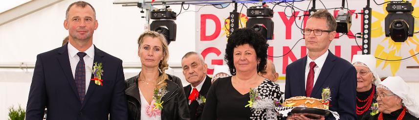 """Na zdjęciu Starostowie Dożynek, wójt Gabriela Placha oraz Tadeusz Lazarek, przewodniczący Rady Gminy z chlebem dożynkowym na scenie, w tle członkowie Zespołu Folklorystycznego """"Goczałkowice"""""""