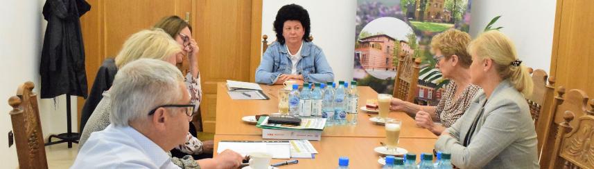 Zdjęcie przedstawia wójta oraz sekretarza gminy podczas spotkania z dyrektorkami publicznych placówek oświatowych, przy stole siedzi sześć osób