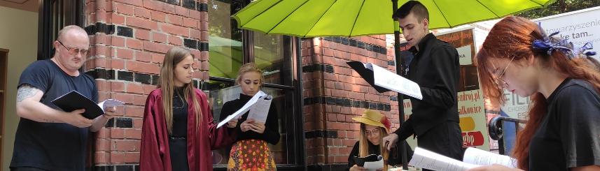 """Zdjęcie przedstawia młodzież czytającą """"Moralność Pani Dulskiej"""" na werandzie przed biblioteką"""