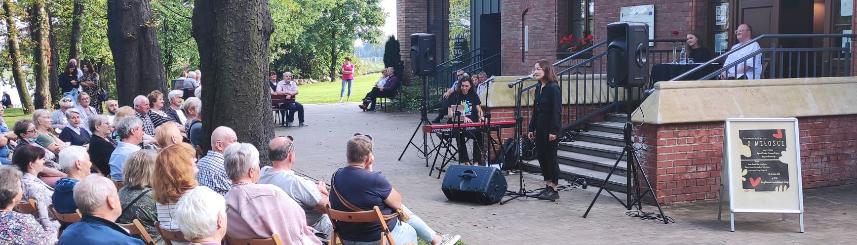 Zdjęcie przedstawia artystkę występującą przed budynkiem Starego Dworca oraz publiczność siedzącą wśród drzew