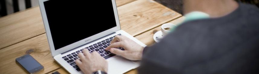 Zdjęcie przedstawia mężczyznę siedzącego przed laptopem, na stoliku znajdują się telefon, notes i filiżanka z kawą