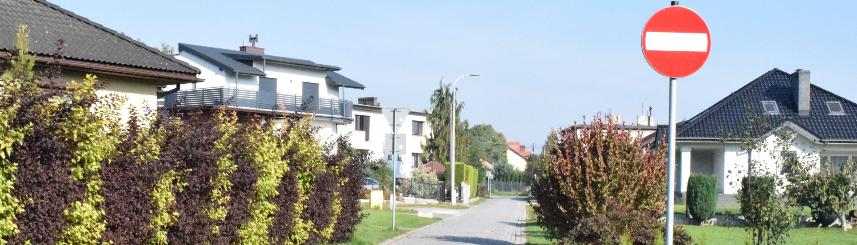 Zdjęcie przedstawia wjazd na ulicę, obok ustawiony znak zakazu wjazdu, w tle - drzewa, krzewy i domy